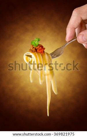 mans hand holding a fork with pasta and Bolognese sauce , black background - stock photo