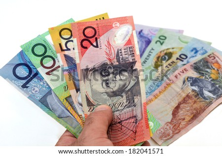 Mans hand holds Australian Dollar banknotes against New Zealand Dollar bank notes. Concept photo of money, banking ,currency and foreign exchange rates.  (Isolated on white background) - stock photo