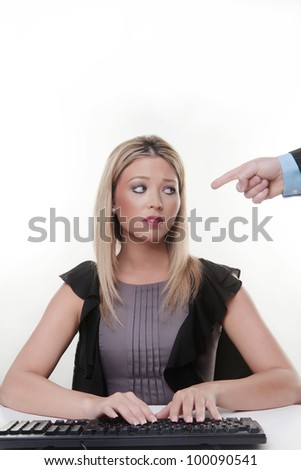 mans hand pointing at a young woman working at her desk she not looking to happy has she done something wrong - stock photo