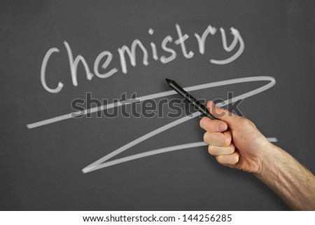 Mans hand pointing to a chemistry message on a chalkboard.