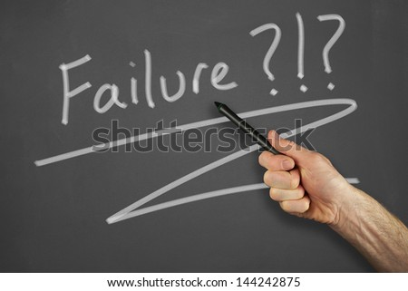 Mans hand pointing to a failure message on a chalkboard.