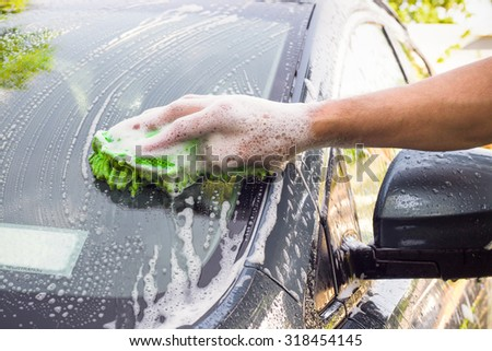 Mans hand washing car with sponge and suds - stock photo
