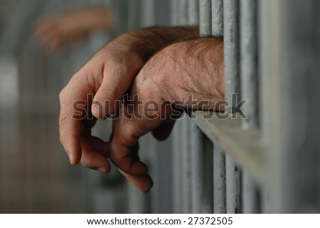 mans hands behind bars in jail or prison - stock photo