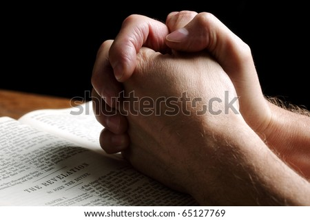 Mans hands folded in prayer over an open Holy Bible - stock photo