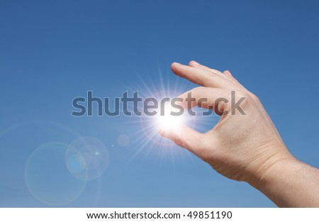 Mans hands holding sun rays - stock photo