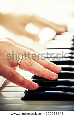 Mans hands playing piano/ selective focus - stock photo