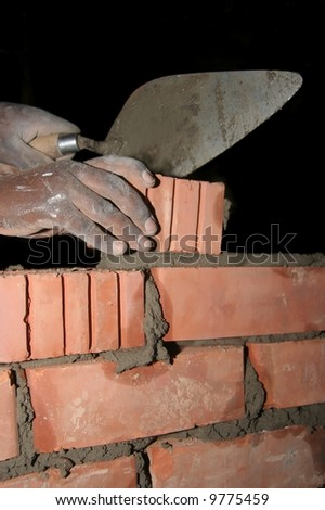 Mans hands with a trowel and laying a brick - stock photo