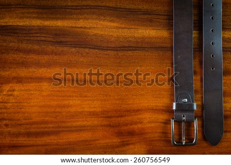 Mans leather brown belt on wooden table - stock photo