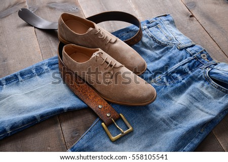 Mans shoes and blue jeans,belt on wood background