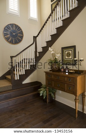 Mansion hallway with modern staircase and luxurious decor. - stock photo