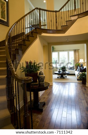 Mansion hallway with winding staircase and luxurious decor.