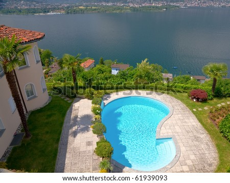 mansion like house with round tower and palm tree an pool resides high over a lake - stock photo