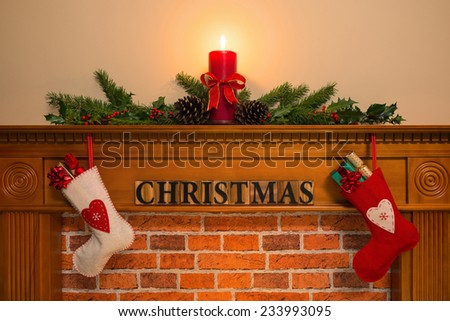 Mantelpiece with red candle and fresh garland made from holly, two stockings full of gifts hanging over the fireplace with the word Christmas. - stock photo