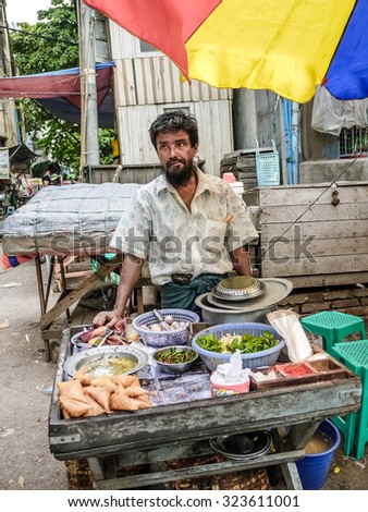 MANTHALAY, MYANMAR - Circa JULY 2012 - Nearby local business area, a man hawker was selling food.