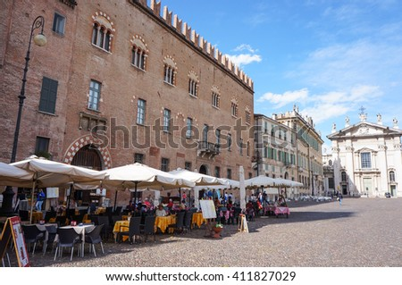 MANTOVA, ITALY - APRIL 18, 2016: People sitting by restaurants on a square with a church in the background - stock photo