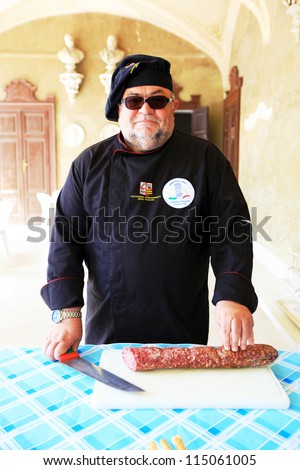 MANTOVA, ITALY - JUNE 13: A chef ready to offer local salami during Golosaria, fair show of food and gastronomy culture June 13, 2010 in Mantova, Italy. - stock photo