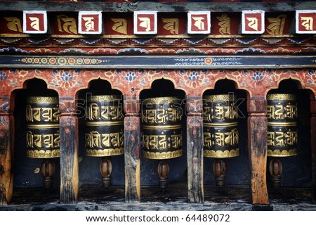 Mantra written on prayer wheels in Bhutan. - stock photo