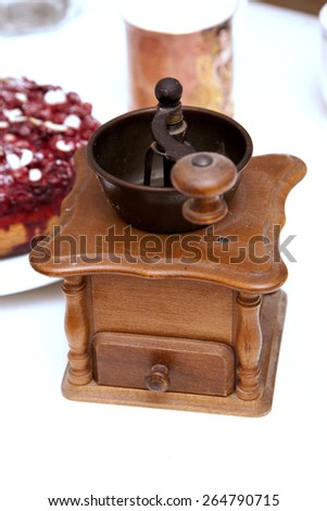 Manual coffee grinder. Fruit cake in the background. - stock photo