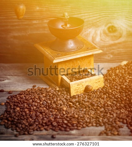 Manual coffee grinder with beans on wooden background - stock photo