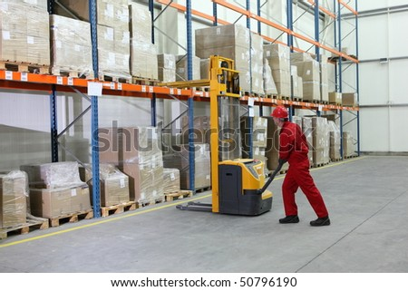 manual forklift operator at work in warehouse - stock photo