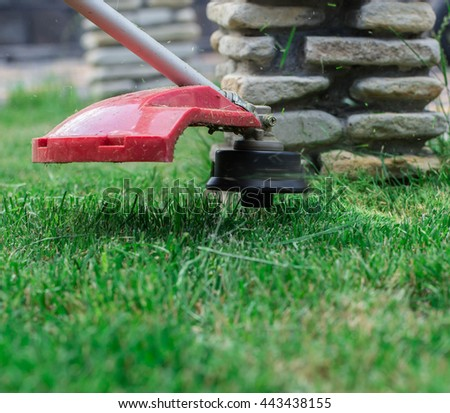 manual lawn mower on the background of green grass, cut grass in not accessible places