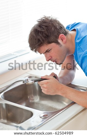 Manual man repairing his sink in the kitchen at home