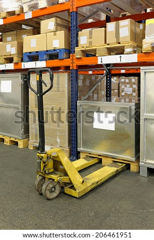 Manual pallet truck in distribution center warehouse - stock photo