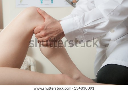 Manual, physio and kinesio therapy techniques performed by a male physiotherapist on a training plastic spine and a female patient - stock photo