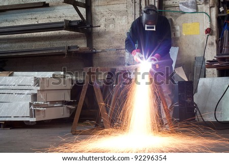 manual plasma cuting in a steel factory lot's of sparks all over - stock photo