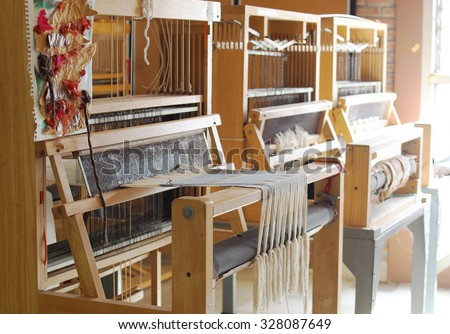manual small weaving machine for making education arts and crafts textiles with local traditional materials and yarns in a university's fashion and textiles workshop in THAILAND - stock photo