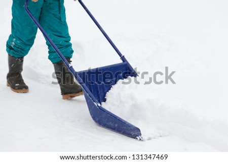 Manual snow removal from driveway using a snow scoop by person wearing boots - stock photo