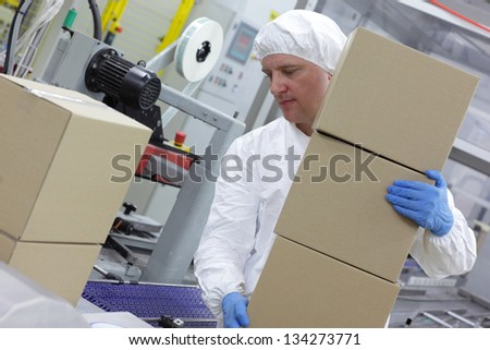 manual worker at production line dealing with boxes - stock photo