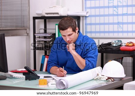Manual worker completing paperwork - stock photo