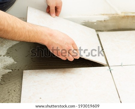 Manual worker covering bathroom floor with caremic tiles. - stock photo