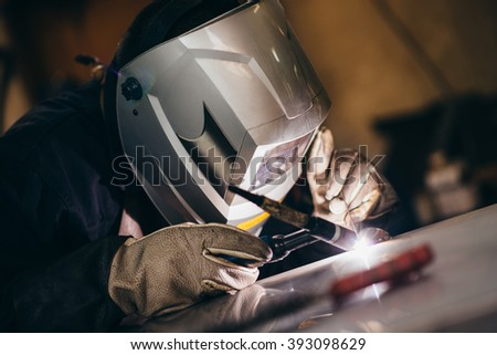 Manual worker doing his hard job using welding mask, tools and machinery on metal. Selective focus on protective mask. - stock photo