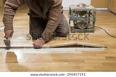 Manual worker fixing wooden floor ruined from moisture and water leak. - stock photo