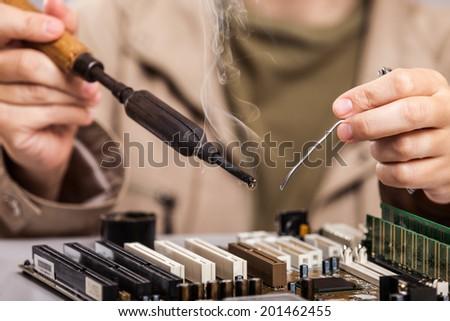 Manual worker human hand holding soldering iron tool repairing computer electronics circuit board - stock photo