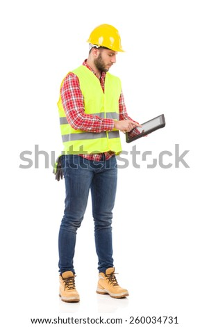 Manual worker in yellow helmet and lime vest using a shockproof digital tablet. Full length studio shot isolated on white.