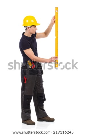 Manual worker measuring. Side view. Full length studio shot isolated on white. - stock photo
