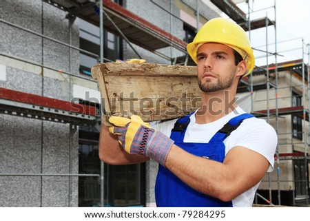 Manual worker on construction site carrying wooden board.