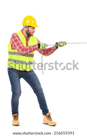 Manual worker pulling a chain. Construction worker in yellow helmet and lime reflective vest pulling a chain. Full length studio shot isolated on white. - stock photo