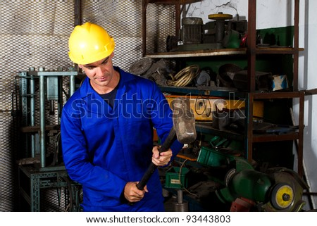 manual worker using big hammer in workshop - stock photo