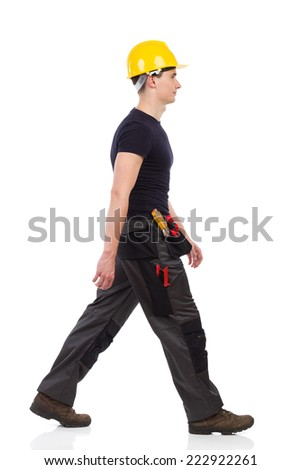 Manual worker walking and looking forward. Full length studio shot isolated on white. - stock photo