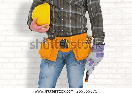 Manual worker wearing tool belt while holding gloves and helmet against white wall - stock photo