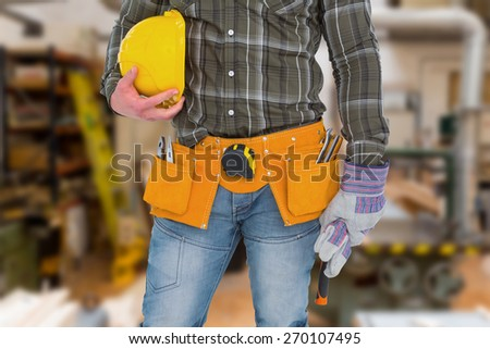 Manual worker wearing tool belt while holding gloves and helmet against workshop - stock photo