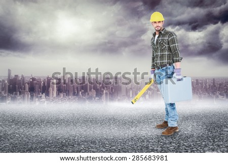 Manual worker with spirit level and toolbox against black road - stock photo