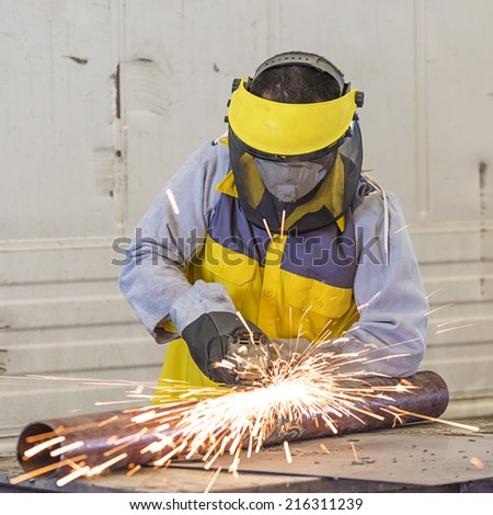 Manual worker work in factory with grinder - stock photo