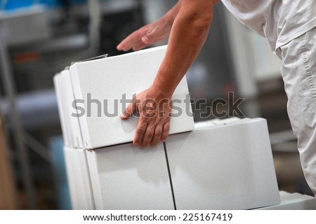 Manual worker working with boxes in factory - stock photo