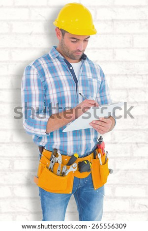 Manual worker writing on clipboard against white wall