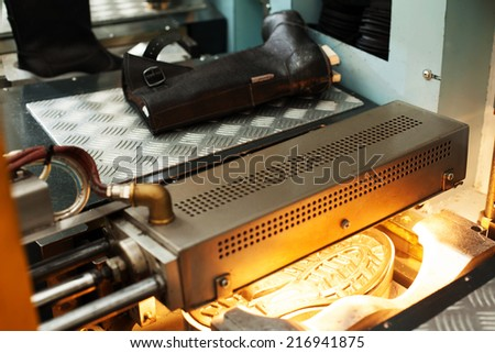 Manufacture of black leather boots - stock photo